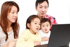 Japanische vierköpfige Familie auf Laptop-Computer Stockbild