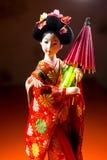 Japanische weibliche Kimonopuppe, die roten Papierregenschirm mit Blumen im Haar und in grünem glühendem Tritium Trinket trägt Lizenzfreie Stockbilder