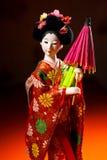 Japanische weibliche Kimonopuppe, die roten Papierregenschirm mit Blumen im Haar und in grünem glühendem Tritium Trinket trägt Stockfotografie