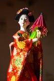 Japanische weibliche Kimonopuppe, die roten Papierregenschirm mit Blumen im Haar und in grünem glühendem Tritium Trinket trägt Lizenzfreies Stockfoto