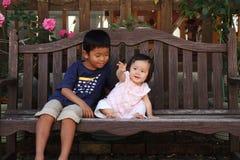 Japanischer Bruder und Schwester auf der Bank Stockbilder