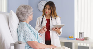 Japanischer Doktor, der den Tablet-Computer spricht mit reifer Frau im Krankenhausbett hält stockbild