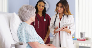 Japanischer Doktor und schwarze Krankenschwester, die mit älterem Frauenpatienten im Krankenhausbett spricht lizenzfreie stockbilder
