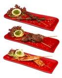 Japanischer Grill Yakitori stellte in eine rote Platte ein Japanischer traditioneller Teller Auf einem wei?en Hintergrund stockfotografie