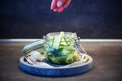 Japanischer Gurkensalat mit Schwarzweiss-Samen des indischen Sesams im Weckglas mit Deckel auf konkretem rundem Behälter, grauer  Stockfotos