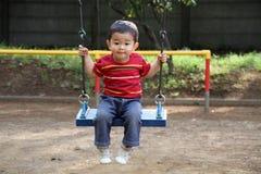 Japanischer Junge auf dem Schwingen Stockfotografie