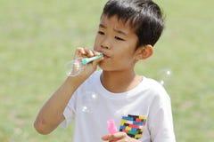 Japanischer Junge, der mit Blase spielt Stockbild