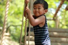 Japanischer Junge, der mit Drahtseil spielt Stockfotografie