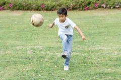 Japanischer Junge, der mit Fußball spielt Lizenzfreie Stockbilder