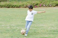 Japanischer Junge, der mit Fußball spielt Stockfoto