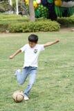 Japanischer Junge, der mit Fußball spielt Lizenzfreies Stockbild