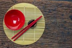 Japanischer Küchengeschirrsatz von roten Essstäbchen, von Schüsseln und von Schale auf Bambusmatte und Holztischhintergrund Lizenzfreie Stockfotografie