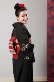 Japanischer Kimono der rückseitigen Ansicht auf glücklichem asiatischem Baumuster Stockfotografie