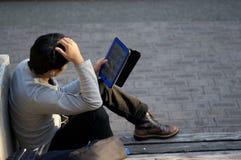 Japanischer Mann genießt seine Tablette auf einer Bank an Kobes Ostpark Higashi Yuenchi in Japan lizenzfreies stockfoto
