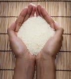 Japanischer Reis in Ihrer Hand auf japanischen Matten stockfotografie