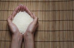 Japanischer Reis in Ihrer Hand auf japanischen Matten stockbilder