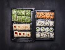 Japanischer Schnellimbiß, Sushi stellte mit zwei variousingredients in den Plastikbehältern auf dunklem rustikalem Hintergrund, D Stockbild