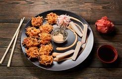 Japanischer Tempurabratenteller, der mit Krabbenstöcken, -soßen und -lachsen dient Bambusessstäbchen auf dunklem Hintergrund Besc stockbild