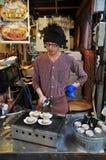 Japanischer Verkäufer brät Muschelkammuschel Stockfotos