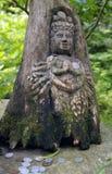 Japanisches hölzernes Schnitzen einer Göttin mit Münzen in einem grünen Wald Lizenzfreies Stockbild