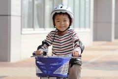 Japanisches Jungenreiten auf dem Fahrrad Stockfotografie