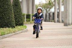 Japanisches Jungenreiten auf dem Fahrrad Stockbilder