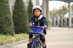 Japanisches Jungenreiten auf dem Fahrrad Lizenzfreie Stockfotografie