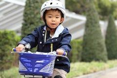 Japanisches Jungenreiten auf dem Fahrrad Stockbild