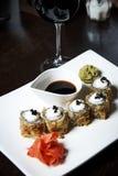 Japanisches Lebensmittel auf einer weißen Platte mit Gläsern Wein lizenzfreie stockfotografie