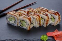 Japanisches Lebensmittel rollt mit Aalfischen auf einem schwarzen Hintergrund Stockfotos