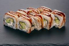 Japanisches Lebensmittel rollt mit Aalfischen auf einem schwarzen Hintergrund Stockbild