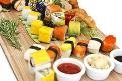 Japanisches Lebensmittel - Sushi, Sashimi, rollt auf einem hölzernen Brett isolat stockbild