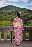 Japanisches Mädchen, das einen Tempel auf bewaldetem Abhang ansieht Stockfoto