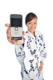 Japanisches Mädchen, das ihren Handy zeigt Stockbild