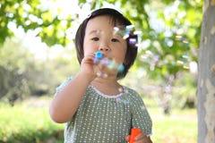 Japanisches Mädchen, das mit Seifenblasen spielt Lizenzfreie Stockfotografie
