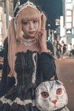Japanisches Mädchen im schwarzen Kostüm und im blonden Tauchhaar gehend bei Harajuku in Beispiel Tokyos Japan des typischen Japan lizenzfreie stockbilder