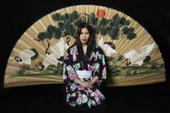 Japanisches Mädchen im traditionellen japanischen Kimono, Griffzweige von ch Lizenzfreies Stockfoto