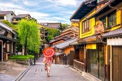 Japanisches Mädchen in Yukata mit rotem Regenschirm in der alten Stadt Kyoto lizenzfreies stockbild