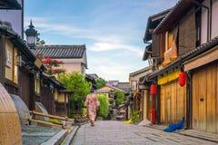Japanisches Mädchen in Yukata mit rotem Regenschirm in der alten Stadt Kyoto stockfotografie