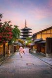 Japanisches Mädchen in Yukata mit rotem Regenschirm in der alten Stadt Kyoto lizenzfreie stockfotografie