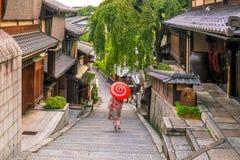 Japanisches Mädchen in Yukata mit rotem Regenschirm in der alten Stadt Kyoto stockbilder