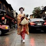 Japanisches maiko, das hinunter die Straße geht stockbild