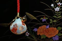 Japanisches Oberteilamulett im Blumenkunsthintergrund Lizenzfreies Stockfoto