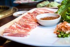 Japanisches Schweinefleisch diente auf einer Platte, die mit Blumen und mouthwatering frischem Wasabi verziert wurde Stockfotos