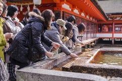Japanisches Volk, das Hand in einem Tempel wäscht Lizenzfreie Stockfotografie