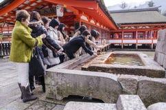 Japanisches Volk, das Hand in einem Tempel wäscht Stockfotografie