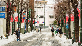Japanisches Volk, das Schnee mit einer Schaufel entfernt Stockfoto
