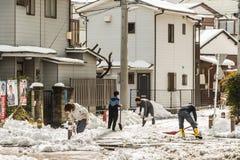 Japanisches Volk, das Schnee mit einer Schaufel entfernt Stockfotografie