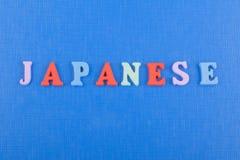 JAPANISCHES Wort auf dem blauen Hintergrund verfasst von den hölzernen Buchstaben des bunten ABC-Alphabetblockes, Kopienraum für  Stockbilder
