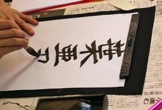 In Japanner die wordt iets geschreven op een blad van document schrijven stock afbeeldingen